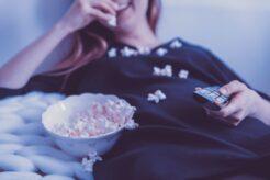 Kvinde ser fjernsyn og spiser popkorn