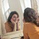 Kvinde smiler og kigger i spejl på sig selv