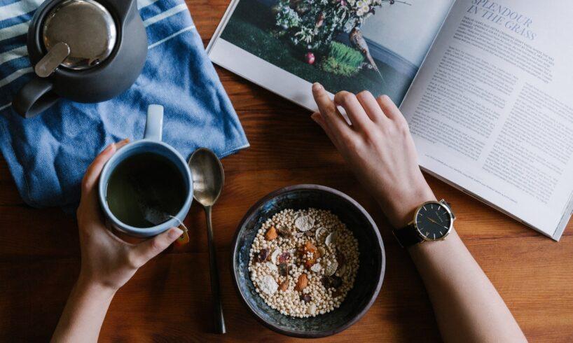 Person drikker kaffe og læser et blad