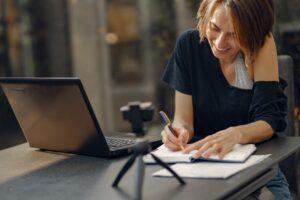 Dame skriver noter i sin notesblok